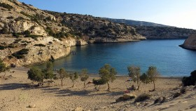Vathy, a small fjord hugs the spectacular waters of the Libyan Sea|The Libyan Sea in the horizon...|||Paximadia island greets you from afar...||